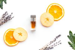 Perfume dulce con fragancia de la fruta Botella de perfume cerca de la manzana, naranja, lavanda, canela en el fondo blanco a imagen de archivo libre de regalías
