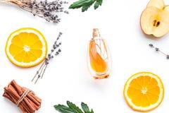 Perfume dulce con fragancia de la fruta Botella de perfume cerca de la manzana, naranja, lavanda, canela en el fondo blanco a fotografía de archivo libre de regalías