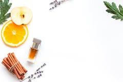 Perfume dulce con fragancia de la fruta Botella de perfume cerca de la manzana, naranja, lavanda, canela en el fondo blanco a fotos de archivo libres de regalías