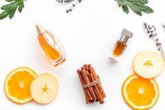 Perfume dulce con fragancia de la fruta Botella de perfume cerca de la manzana, naranja, lavanda, canela en el fondo blanco a foto de archivo