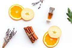 Perfume dulce con fragancia de la fruta Botella de perfume cerca de la manzana, naranja, lavanda, canela en el fondo blanco a fotos de archivo