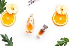 Perfume dulce con fragancia de la fruta Botella de perfume cerca de la manzana, naranja, lavanda en la opinión superior del fondo foto de archivo libre de regalías