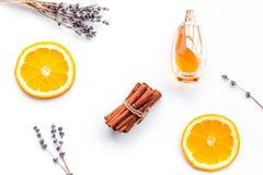 Perfume dulce con fragancia de la fruta Botella de perfume cerca de la naranja, lavanda, canela en la opinión superior del fondo  imagenes de archivo