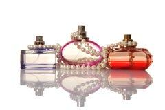 Perfume en botellas de cristal y beeds de la perla Fotografía de archivo libre de regalías