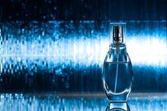 Perfume en fondo azul Foto de archivo libre de regalías