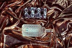 Perfume en fondo del oro Imagen de archivo libre de regalías