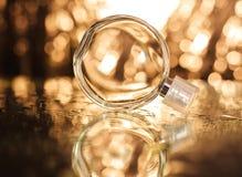 Perfume en fondo del oro Imágenes de archivo libres de regalías
