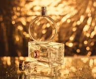 Perfume en fondo del oro Fotos de archivo