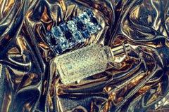 Perfume en un fondo del oro Imágenes de archivo libres de regalías
