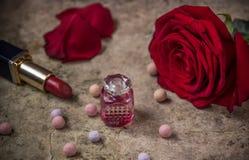 Perfume en una botella de cristal, una flor de la rosa del rojo y un lápiz labial Imagen de archivo libre de regalías