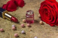 Perfume en una botella de cristal, una flor de la rosa del rojo y un lápiz labial Imagenes de archivo