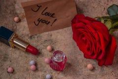 Perfume en una botella de cristal, una flor de la rosa del rojo y un lápiz labial Observe los wi Imagen de archivo libre de regalías