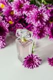 Perfume with floral scent. Perfume bottle and pink chrysanthemums on a white background stock photography