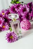 Perfume with floral scent. Perfume bottle and pink chrysanthemums on a white background stock photo
