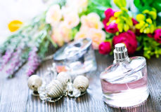 Perfume. And flowers on the wooden table Stock Photos