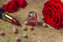 Perfume in a glass bottle, red rose flower and lipstick Stock Images