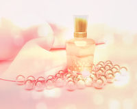 Perfume in a glass bottles and pearl beads on light pink. Stock Photos