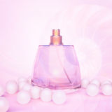 Perfume in a glass bottles and pearl beads on pink. Royalty Free Stock Photos
