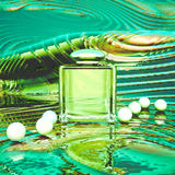 Perfume in a glass bottles and pearl beeds on a color background Stock Image