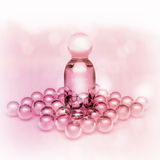Perfume in a glass bottles and pearl beeds on light pink. Royalty Free Stock Images