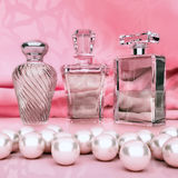 Perfume in a glass bottles and pearl on pink background. Square vector illustration