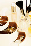 Perfume, jewelry and makeup brushes on a  table, close-up Stock Photos