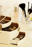 Perfume, jewelry and makeup brushes on a  table, close-up Stock Images