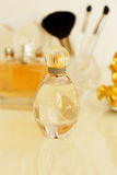 Perfume, jewelry and makeup brushes on a  table, close-up Royalty Free Stock Photo
