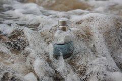 Perfume la botella en espuma del mar en el borde del agua imagenes de archivo