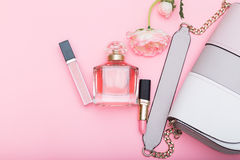 Perfume, lip gloss, lipstick and bag on a pink background Royalty Free Stock Photography