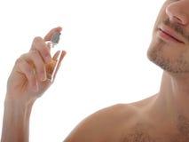 Perfume masculino joven del aerosol del tiro macro en su piel Imágenes de archivo libres de regalías