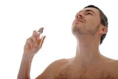 Perfume masculino joven del aerosol en su piel Foto de archivo
