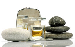 Perfume on the mirror and stones Royalty Free Stock Photography