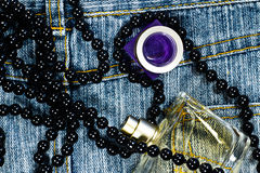 Perfume and necklace on blue jeans Stock Photo