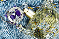 Perfume and necklace on jeans Stock Images