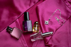 Perfume and a necklace on a red blouse Royalty Free Stock Photo