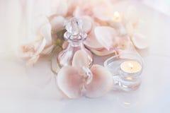 Perfume o botella de aceite aromática rodeada por las flores y las velas Foto de archivo libre de regalías