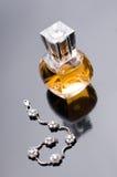 Perfume para mulheres e o bracelete de prata no cinza Foto de Stock Royalty Free