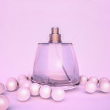 Perfume and pearl beeds on pink. Royalty Free Stock Photo