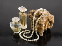 Perfume and pearl necklace. On a black background Royalty Free Stock Photography