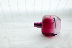 Perfume. Pink bottle of perfume lies beautifully on a white background Royalty Free Stock Photos