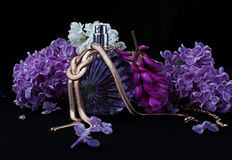 Perfume and purple flowers Stock Photography