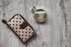 Perfume, purse. Composition, perfume in a glass bottle and a purse on a wooden background stock photos