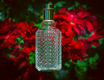Perfume and red flowers Stock Photos