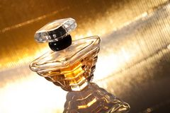 Perfume with reflection on gold background Royalty Free Stock Photos