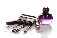Perfume, rimel, sombra de ojos, lápiz labial y cepillos foto de archivo libre de regalías