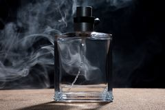 Perfume and smoke. A perfume bottle with a floating smoke behind. Exotic feeling Royalty Free Stock Photo