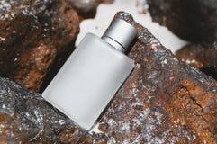 Bottle of male perfume on stone stock photography