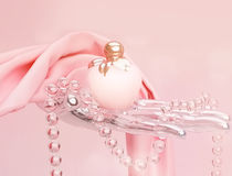 Perfume, a string of beads and pink silk scarf is located on a p Stock Photos