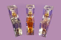 Three bottles of perfume on the lilac color background. Perfume in three little glass bottles on the lilac color background stock images
